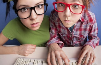Two girls with glasses at computer