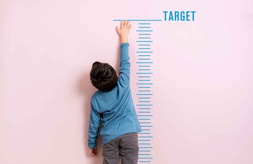 Boy reaching to target line on a height chart