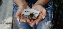 Hands holding coins and paper that says make a change