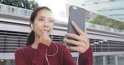 asian woman speaking into her headphones while participating in a virtual event.